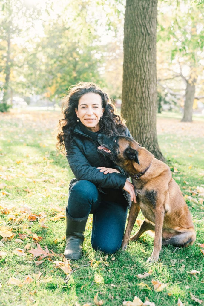 Souha kneeling in the park with a dog